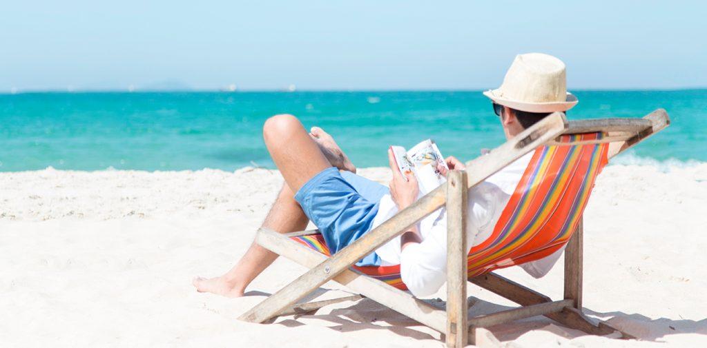 Hombre leyendo libro frente al mar